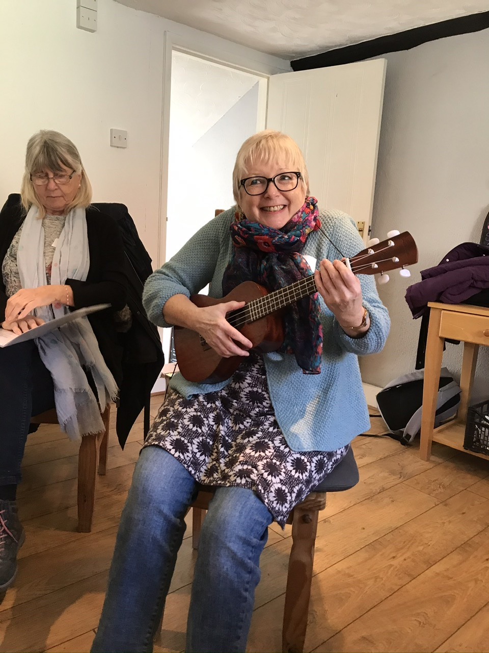 A photo from one of the taster workshops. For this workshop, the group were trying singing with singing teacher, Sally Rose. In this photo Sally is grinning while sat on a chair with a little guitar.
