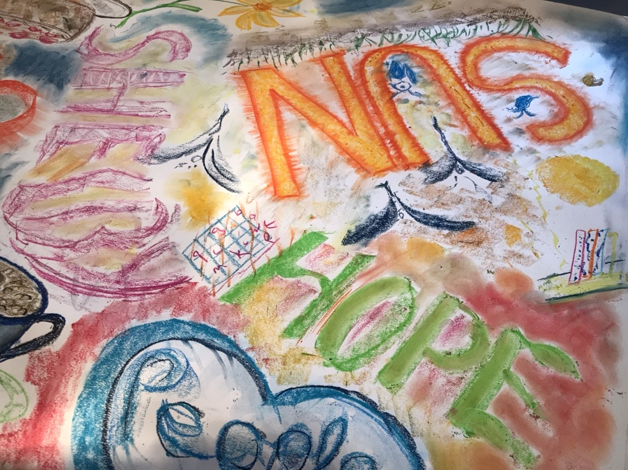 """A photo from one of the taster workshops. For this workshop, the group were trying pastels. In this photo, a large piece of paper has been covered in drawings in pastel, including images of coffee cups, flowers and words like """"sun"""" and """"hope""""."""