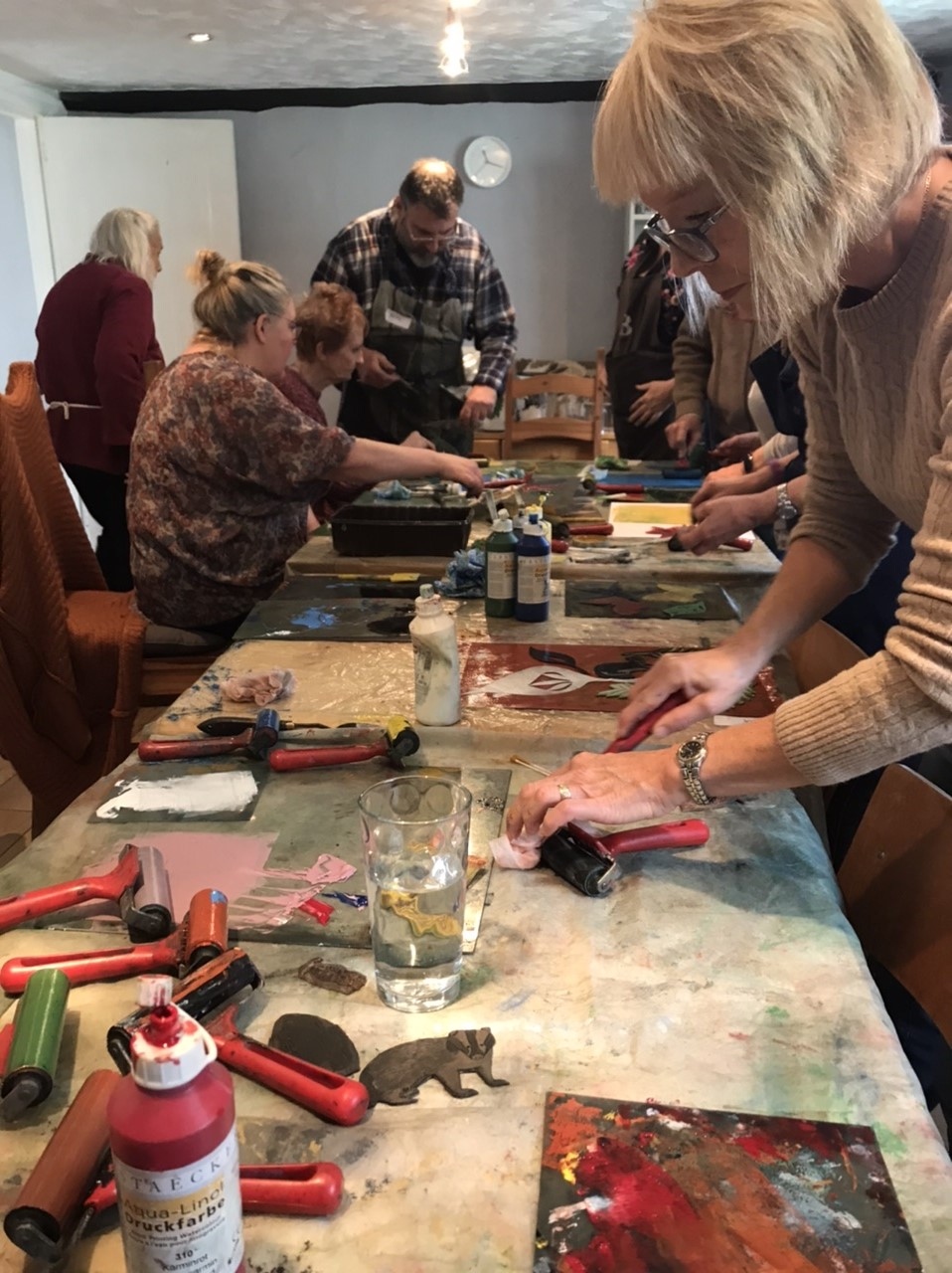 A photo from one of the taster workshops. For this workshop, the group were trying screenprinting. The group are sitting and standing around a large long table, with rollers, paint and printing stamps scattered on the table.