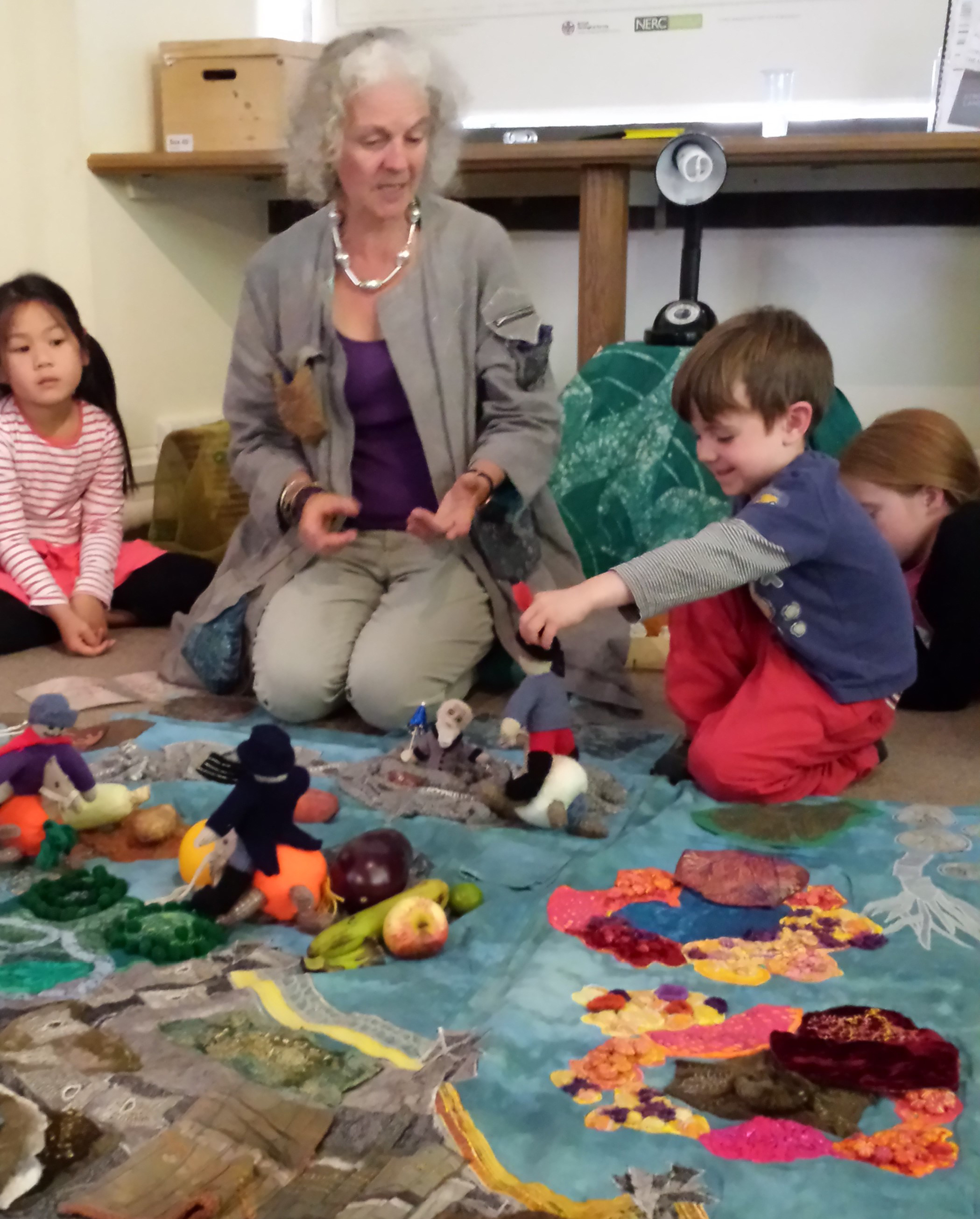 A photo of Marion engaging with and telling a story to small children on a colourful mat at a playgroup.